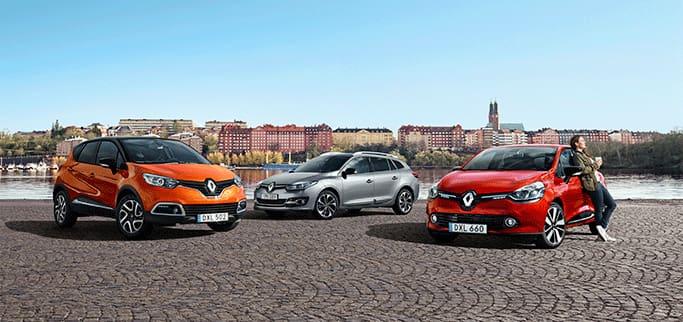 Tre Renault personbilar parkerade på en lastkaj. En kvinna står lutad mot en av dem och dricker kaffe.