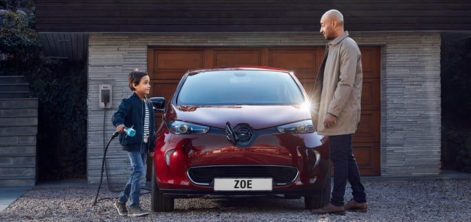 Ett barn och en vuxen man laddar en röd Renault Zoe på uppfarten.