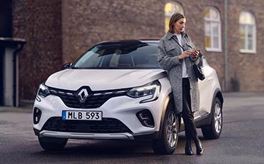 Kvinna lutar sig mot en vit Renault Captur