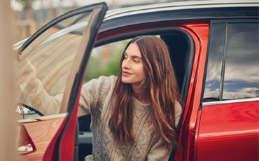 Kvinna sitter i förarsätet på en röd Renault