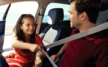 Barn hjälper till att sätta fast bilbälte på förare